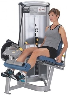 Mulher fazendo a extensão de joelhos em uma máquina